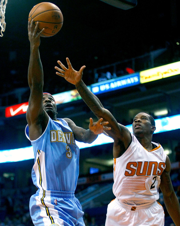 . Denver Nuggets point guard Ty Lawson (3), left, drives past Phoenix Suns point guard Eric Bledsoe (2) in the first quarter during an NBA basketball game on Friday, Nov. 8, 2013, in Phoenix. (AP Photo/Rick Scuteri)