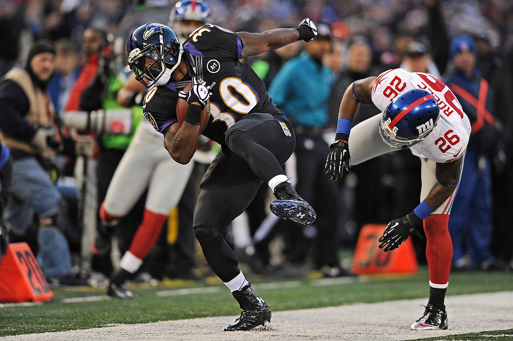 . Running back Bernard Pierce #30 of the Baltimore Ravens is hit out of bounds by safety Antrel Rolle #26 of the New York Giants in the first quarter at M&T Bank Stadium on December 23, 2012 in Baltimore, Maryland. (Photo by Patrick Smith/Getty Images)