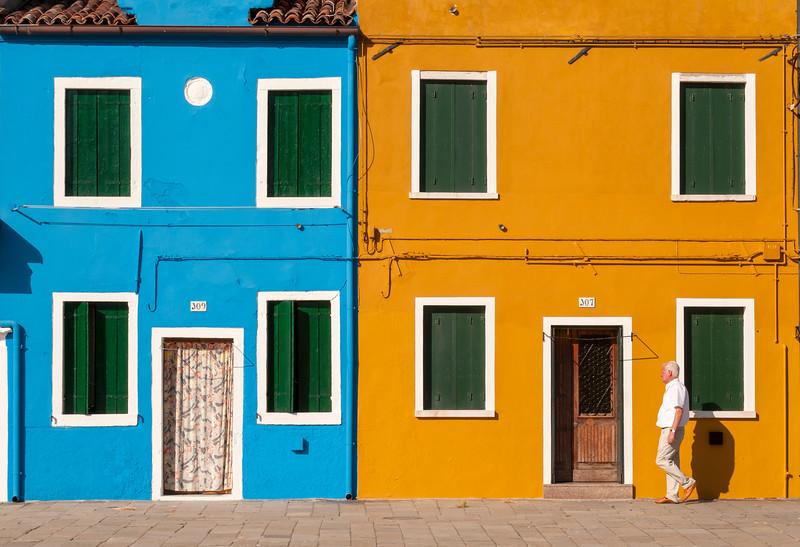 Man Passes Brightly Painted Houses, Piazza Baldassarre Galuppi, Burano, Venice, Veneto, Italy
