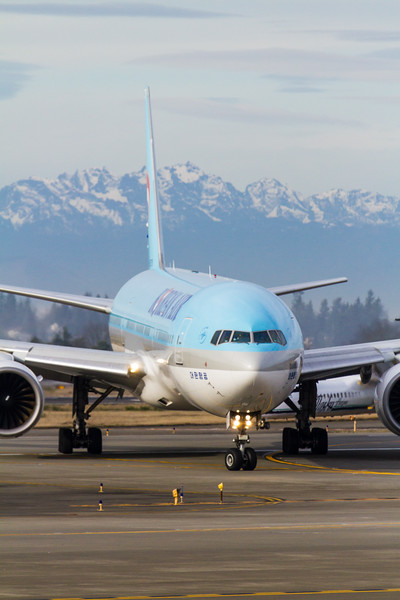 A Korean Air Boeing 777-300ER taxis at SeaTac International Airpot on a slightly cloudy day with the Olympic Mountains in the background