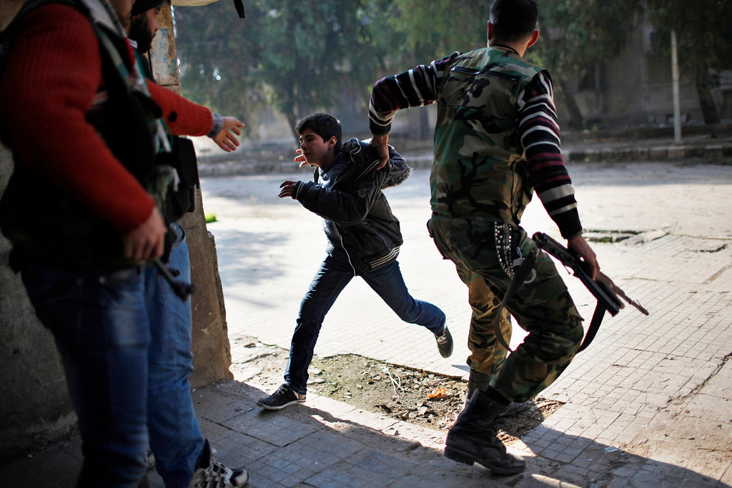 . A Free Syrian Army fighter pulls a boy off the street as a sniper fires during fighting with forces loyal to Syrian President Bashar el-Assad in Aleppo city December, 31, 2012. REUTERS/Ahmed Jadallah