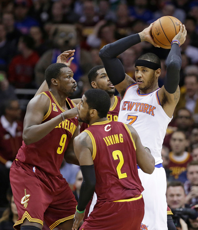 . New York Knicks\' Carmelo Anthony (7) looks for help from a teammate under pressure from Cleveland Cavaliers\' Kyrie Irving (2), Luol Deng (9) and Tristan Thompson (13) during the first quarter of an NBA basketball game Saturday, March 8, 2014, in Cleveland. (AP Photo/Tony Dejak)