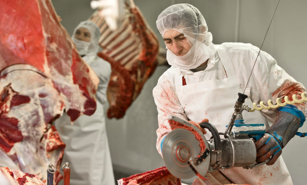 Description of . Workers handle meat at the Doly-Com abattoir, one of the two units checked by Romanian authorities in the horse meat scandal, in the village of Roma, northern Romania, Tuesday, Feb. 12, 2013. On Monday, Romanian officials scrambled to defend two plants implicated in the scandal, saying the meat was properly declared and any fraud was committed elsewhere. (AP Photo/Vadim Ghirda)