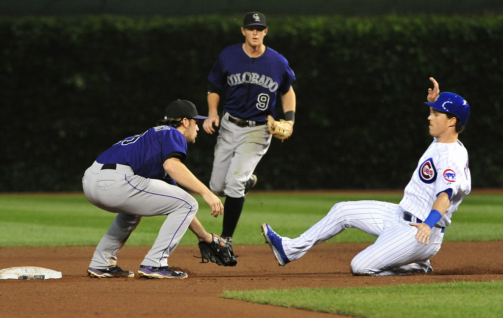 . CHICAGO, IL - JULY 30:  Chris Coghlan #8 of the Chicago Cubs is tagged out by Charlie Culberson #23 of the Colorado Rockies during the fourth inning on July 30, 2014 at Wrigley Field in Chicago, Illinois.  (Photo by David Banks/Getty Images)