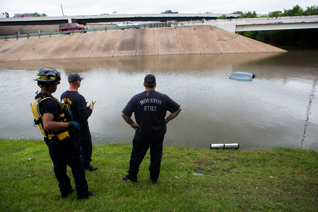 . The Houston Fire Department checks a flooded car on the frontage road in between South Loop West Freeway and South Post Oak Road near the Willow Waterhole Bayou, Tuesday, May 26, 2015, in Houston. Floodwaters kept rising Tuesday across much of Texas as storms dumped almost another foot of rain on the Houston area, stranding hundreds of motorists and inundating the highways. (Marie D. De Jesus/Houston Chronicle via AP)