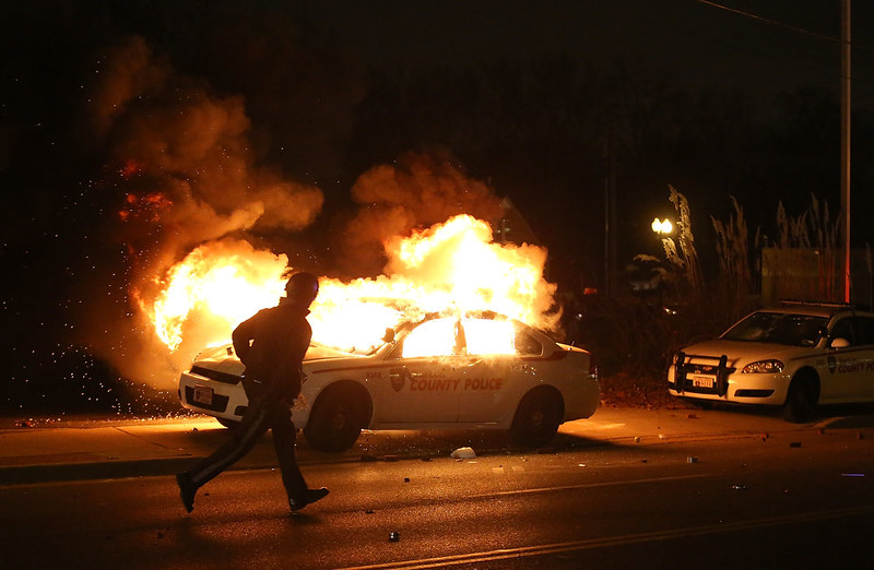 . A police officer runs by a burning police car during a demonstration on November 24, 2014 in Ferguson, Missouri. A St. Louis County grand jury has decided to not indict Ferguson police Officer Darren Wilson in the shooting of Michael Brown that sparked riots in Ferguson, Missouri in August.  (Photo by Justin Sullivan/Getty Images)