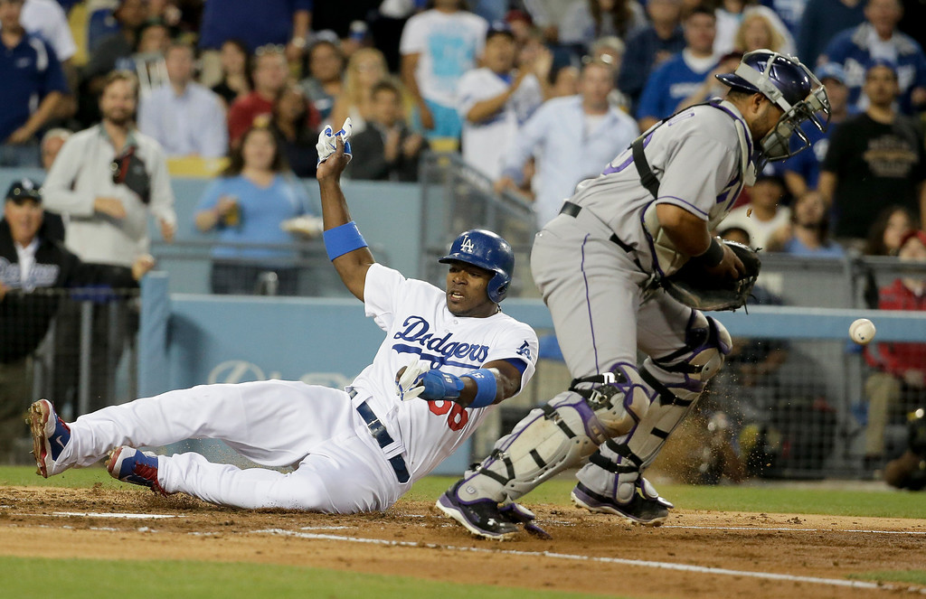 . Los Angeles Dodgers\' Yasiel Puig, left, scores past Colorado Rockies catcher Wilin Rosario on a double Adrian Gonzalez by during third inning of a baseball game in Los Angeles, Wednesday, June 18, 2014. (AP Photo/Chris Carlson)