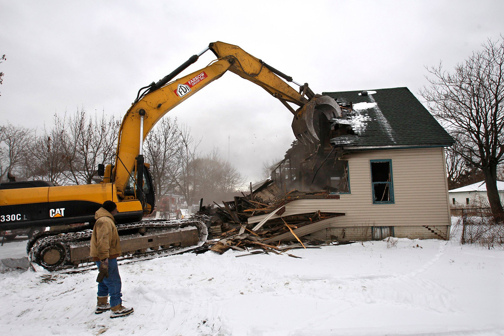 . In this Feb. 12, 2010  photo, a burned out house is demolished in Detroit. After decades of decline that gutted many once-vibrant neighborhoods, Detroit is preparing a radical renewal effort on a scale never attempted in this country: returning a large swath of the city to fields or farmland, much like it was in the middle of the 19th century. Under plans now being refined, demolition crews would move through the most desolate and decayed areas of urban Detroit with building-chomping excavators, reducing houses to rubble. (AP Photo/Carlos Osorio)