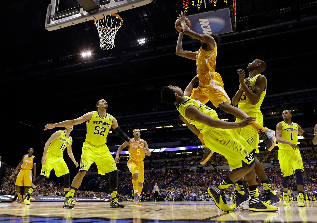. Tennessee\'s Jordan McRae shoots over Michigan\'s Derrick Walton Jr. and Caris LeVert (23) during the second half of an NCAA Midwest Regional semifinal college basketball tournament game Friday, March 28, 2014, in Indianapolis. (AP Photo/David J. Phillip)