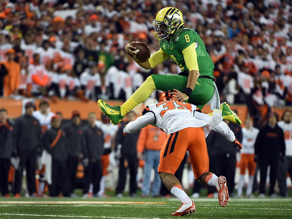 . Quarterback Marcus Mariota #8 of the Oregon Ducks hurdles safety Justin Strong #39 of the Oregon State Beavers during the first quarter of the game at Reser Stadium on November 29, 2014 in Corvallis, Oregon.  (Photo by Steve Dykes/Getty Images)