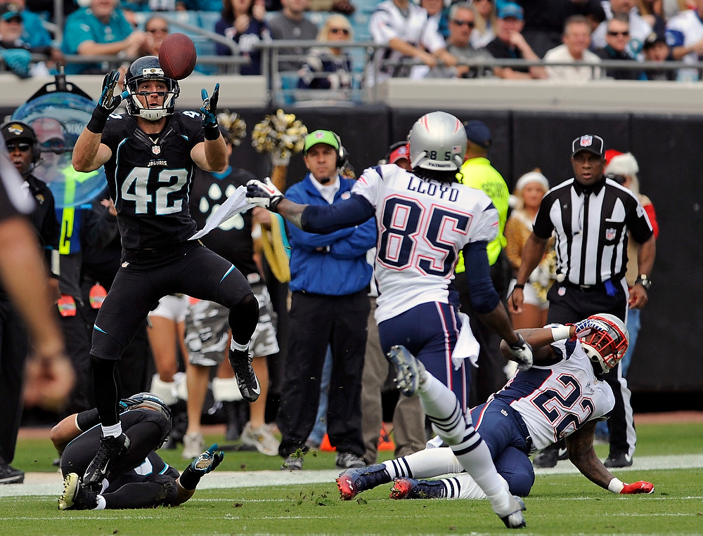 . Jacksonville Jaguars free safety Chris Prosinski (42) intercepts a pass in front of New England Patriots wide receiver Brandon Lloyd (85) and running back Stevan Ridley (22) during the first half of an NFL football game on Sunday, Dec.  23, 2012, in Jacksonville, Fla. (AP Photo/Stephen Morton)