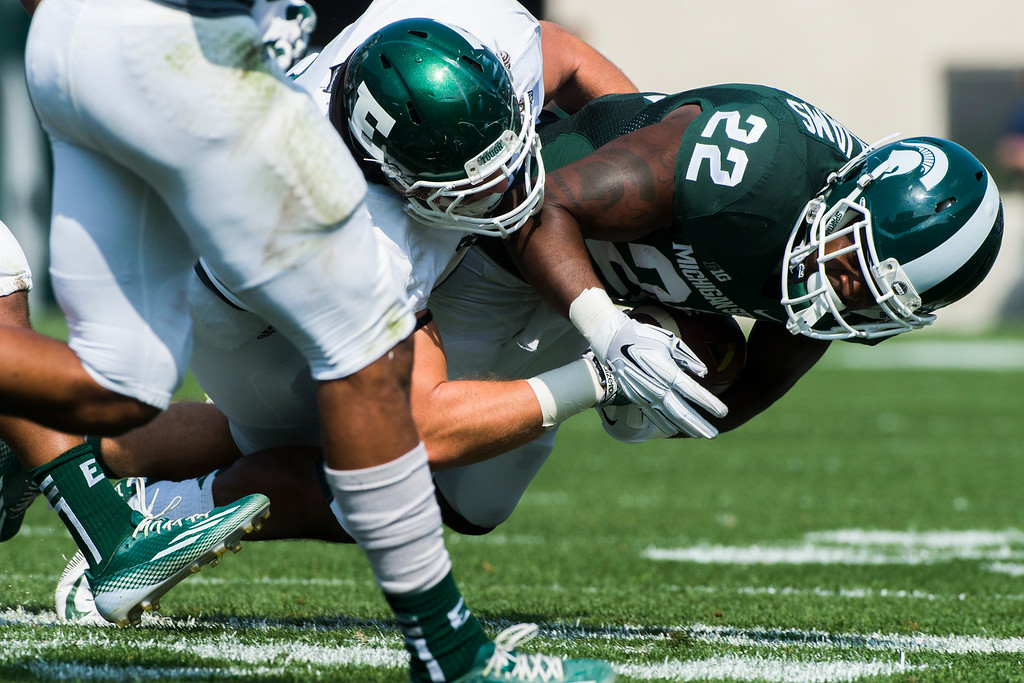 . Eastern Michigan linebacker Hunter Matt tackles Michigan State sophomore running back Delton Williams during the first half on Saturday, Sept. 20, 2014 at Spartan Stadium in East Lansing, Mich. (AP Photo/The Flint Journal, Jake May)
