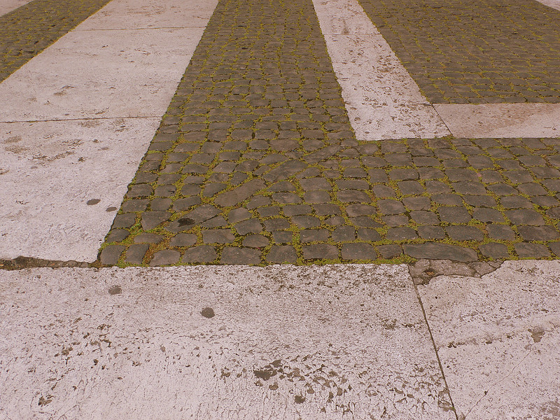 Roman streetscape : A close-up of a cobbled Roman street near Trajan's park, mortared with the mossy grass of early spring.