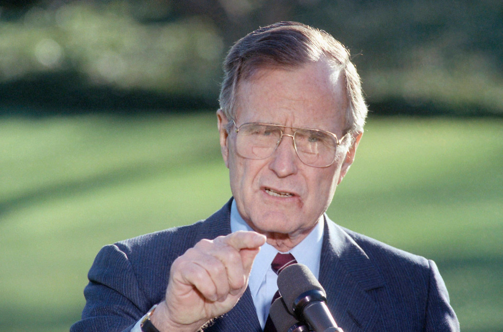 ". 1990: George H.W. Bush. U.S. President George H. Bush makes a statement at the White House, Friday, Dec. 14, 1990 in Washington prior to his departure for Camp David, Md. Bush said he had offered 15 dates for Secretary of State James A. Baker III to visit Iraq leader Saddam Hussein on or prior to January 12, three days before a UN deadline for Iraq to withdraw from Kuwait, and ""that deadline I real.\"" The White House declined to say what the mark on the lower lip of Bush is. (AP Photo/Barry Thumma)"