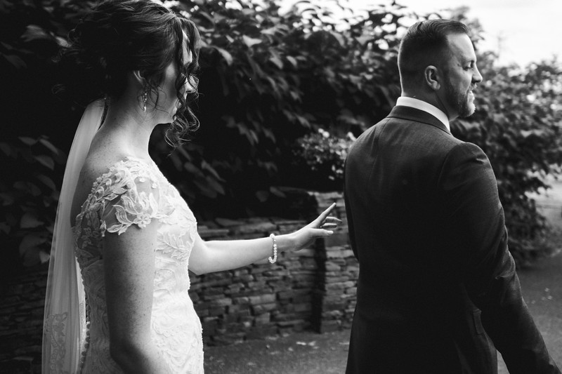 The about to gently touch the grooms shoulder with a single finger as the groom starts to turn towards her.
