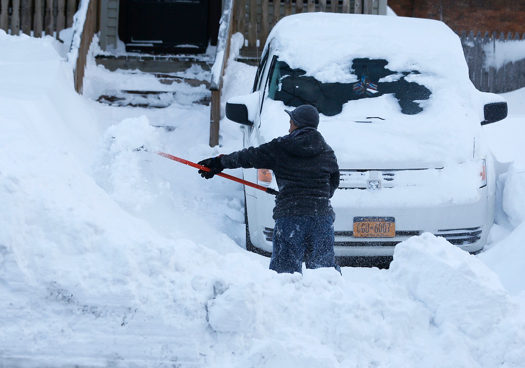 . Maria Formholtz shovels her parking area in her south Buffalo neighborhood on Thursday, Nov. 20, 2014, in Buffalo, N.Y.   A new blast of lake-effect snow pounded Buffalo for a third day piling more misery on a city already buried by an epic, deadly snowfall that could leave some areas with nearly 8 feet of snow on the ground when it\'s all done. (AP Photo/Mike Groll)