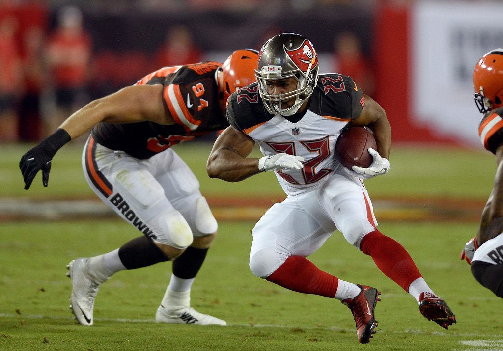. Tampa Bay Buccaneers running back Doug Martin (22) eludes Cleveland Browns defensive end Carl Nassib (94) during the second quarter of an NFL preseason football game Saturday, Aug. 26, 2017, in Tampa, Fla. (AP Photo/Jason Behnken)