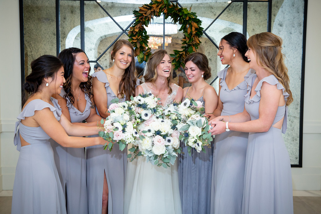briesmaids wearing lavender full-length dresses holding white and blush rose bouquetes while smiling at the bride