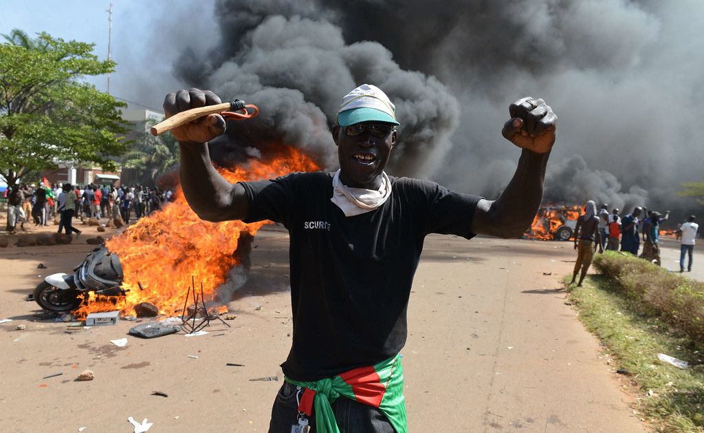 . Protesters stand outside the parliament in Ouagadougou on October 30, 2014 as cars and documents burn outside. Hundreds of angry demonstrators in Burkina Faso stormed parliament on October 30 before setting it on fire in protest at plans to change the constitution to allow President Blaise Compaore to extend his 27-year rule. ISSOUF SANOGO/AFP/Getty Images