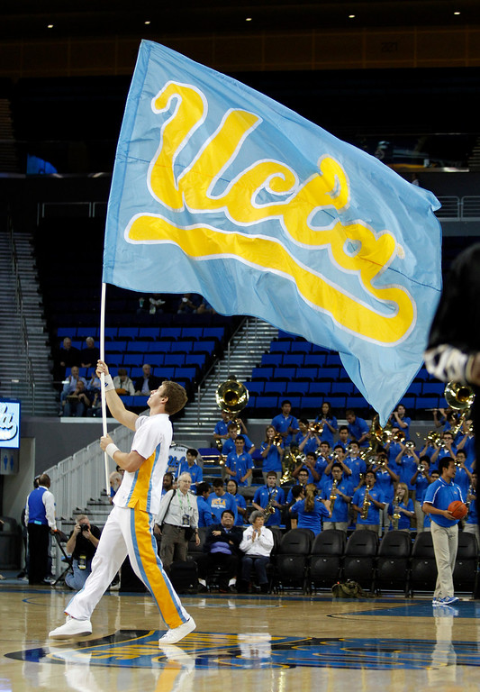 . UCLA cheerleader displays a team banner prior to their NCAA college basketball game against Oakland Tuesday, Nov. 12, 2013, in Los Angeles. UCLA won the game 91-60.  (AP Photo/Alex Gallardo)