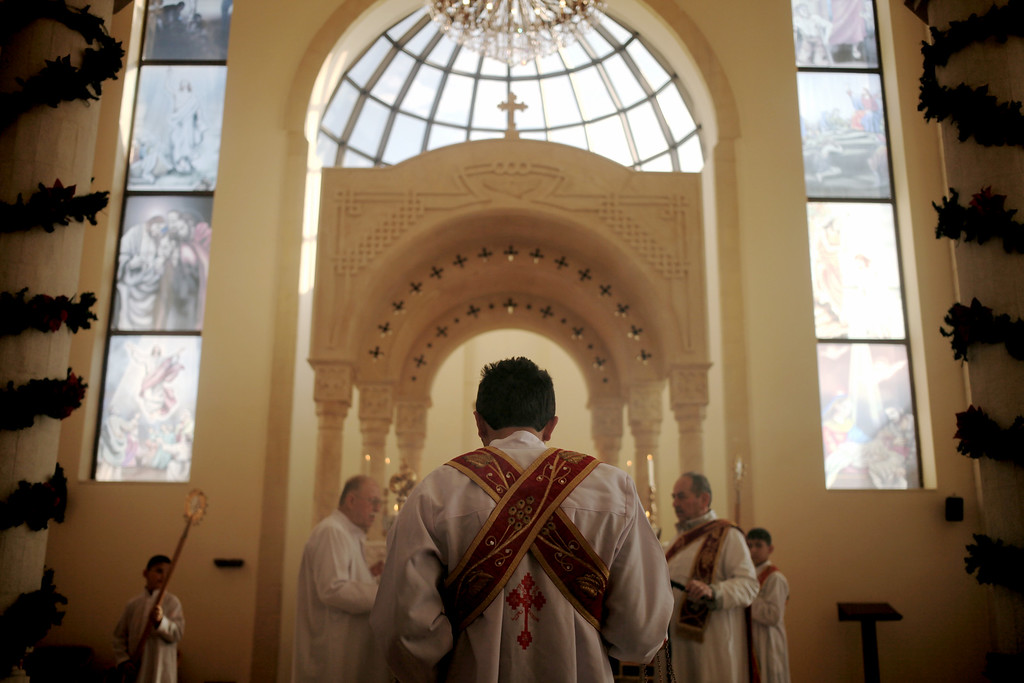 . Clergy conduct morning Christmas mass at the Saint Afram Syrian Orthodox Church in Amman, Jordan, Wednesday, Dec. 25, 2013. Syrian and Iraqi Orthodox Christian families prayed for peace in their countries. (AP Photo/Mohammad Hannon)