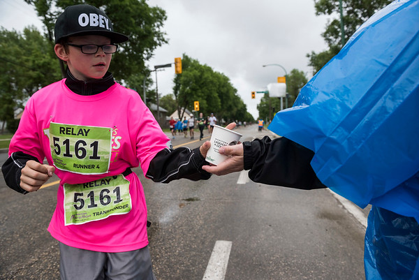 DAVID LIPNOWSKI / WINNIPEG FREE PRESS  Manitoba Marathon participants run and grab water on Harrow Street Sunday June 18, 2017.
