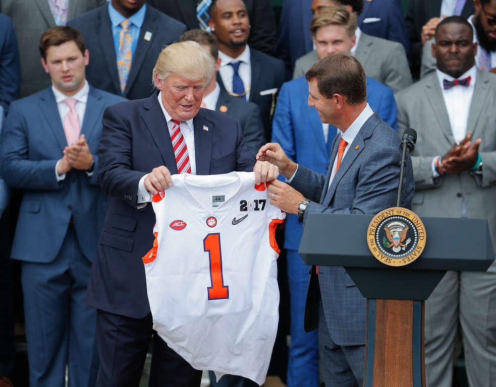 . President Donald Trump holds up a jersey given to by head coach Dado Swinney, right, as he welcomed the 2016 NCAA Football National Champions Clemson University Tigers, Monday, June 12, 2017, during a ceremony on the South Lawn of the White House in Washington. (AP Photo/Pablo Martinez Monsivais)