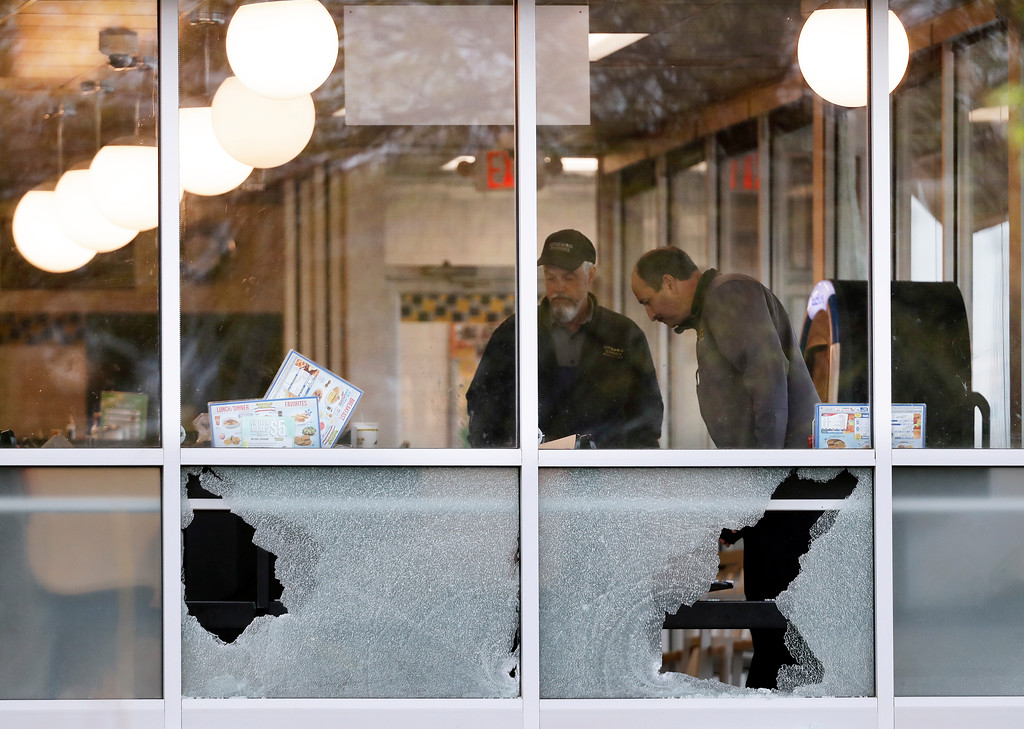 . People look over the area near a window shot out at a Waffle House restaurant Sunday, April 22, 2018, in Nashville, Tenn. At least four people died after a gunman opened fire at the restaurant early Sunday. (AP Photo/Mark Humphrey)