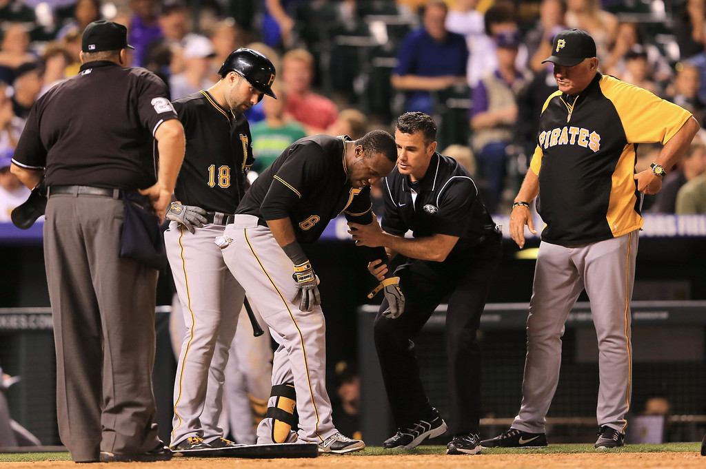 . DENVER, CO - AUGUST 10:  Starling Marte #6 of the Pittsburgh Pirates is attended to after being hit by a pitch by Josh Outman #88 of the Colorado Rockies in the seventh inning at Coors Field on August 10, 2013 in Denver, Colorado.  (Photo by Doug Pensinger/Getty Images)