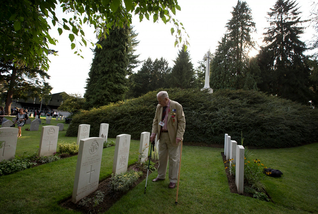 . British Major Maurice French, 84, of Heytesbury in Wiltshire, stands in front of his uncles grave, World War I first Victoria Cross recipient Maurice Dease, during a commemoration ceremony to mark the 100th anniversary of the outbreak of World War I at the St. Symphorien Cemetery in St. Symphorien, Belgium on Monday, Aug. 4, 2014. The cemetery was established by the German Army as a final resting place for British and German soldiers killed at the Battle of Mons. Among those buried is Pvt. John Parr of the Middlesex Regiment, the first British soldier to be killed in action on the Western Front. (AP Photo/Virginia Mayo)