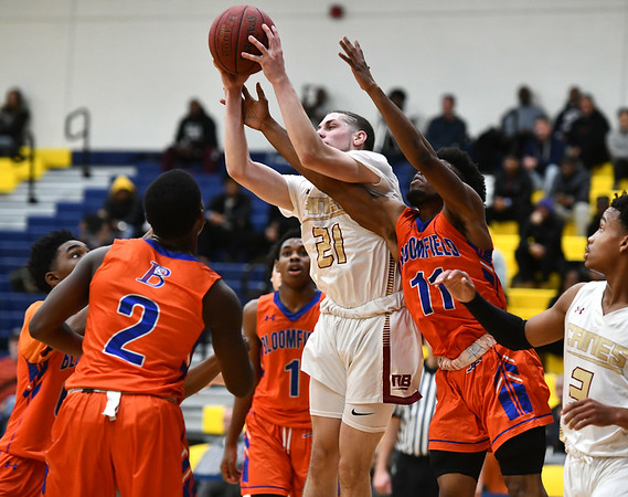 12/21/2019 Mike Orazzi | StafrNew Britain's Nyzaiah Diaz (21) and Bloomfield's Justine Guthrie (1) during the GHPA High School Basketball Classic at Trinity College on Saturday. r