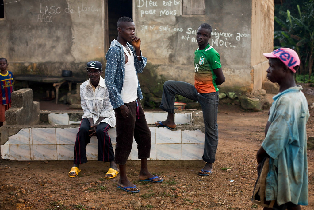 . In this photo taken Sunday Nov. 23, 2014, youth hang out in the Guinean village of Meliandou, some 400 miles (600 kms) south-east of Conakry, Guinea, believed to be Ebola\'s ground zero. (AP Photo/Jerome Delay) .
