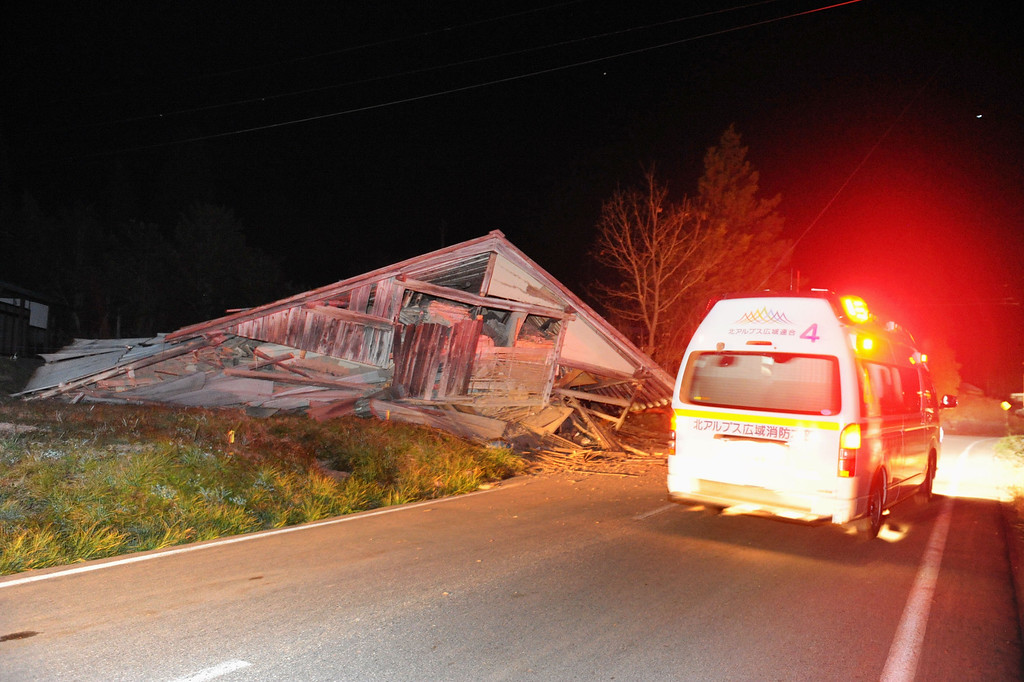 . A fire department vehicle drives past a warehouse collapsed by a strong earthquake in Hakuba, Nagano Prefecture, central Japan, Saturday, Nov. 22, 2014. The magnitude-6.8 earthquake struck the mountainous area of central Japan Saturday night, causing at least one building to collapse and injuring several people, according to Japanese media reports. No tsunami warning was issued. (AP Photo/Shinano Mainichi Shimbun via Kyodo News)