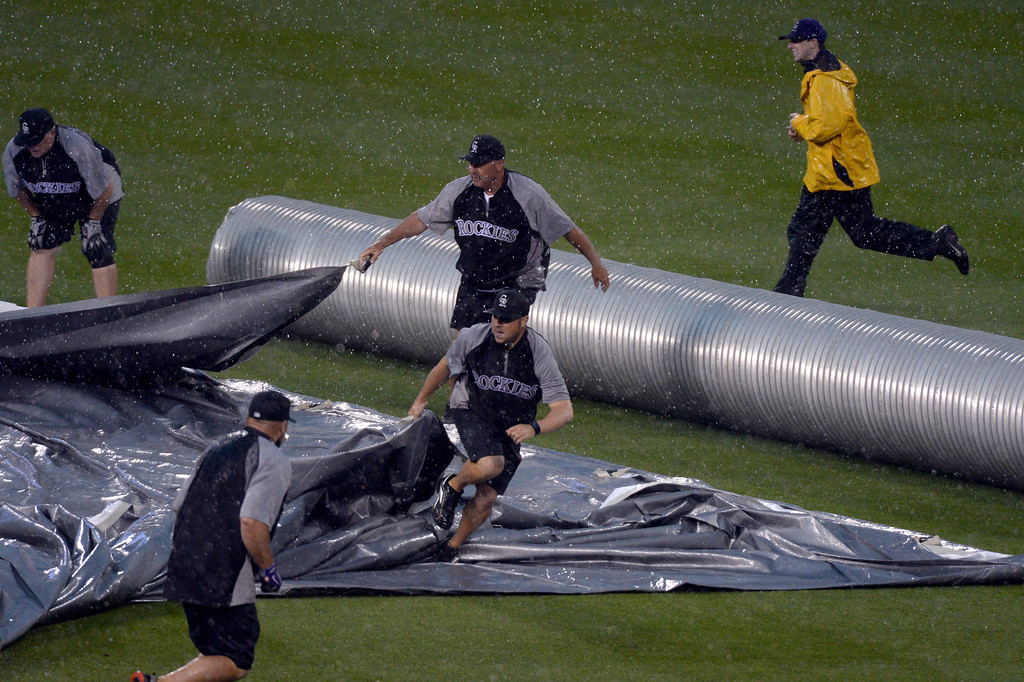 . DENVER, CO - MAY 22: Grounds crew scramble to get the infield covered during a second rain delay during the Colorado Rockies San Francisco Giants game May 22, 2014 at Coors Field. (Photo by John Leyba/The Denver Post)