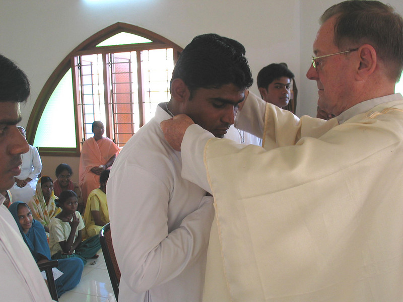 Fr. Martin places the profession cross around Bhaskar's neck.