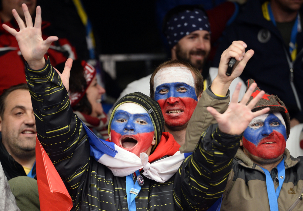 . Russian supporters cheers during the Men\'s Skeleton Flower Ceremony at the Sanki Sliding Center in Rosa Khutor during the Sochi Winter Olympics on February 15, 2014. (LIONEL BONAVENTURE/AFP/Getty Images)