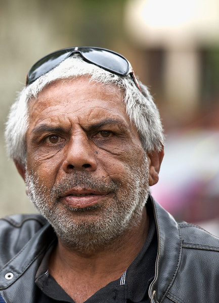 Indigenous Australian Elder looking at camera with a blurred background