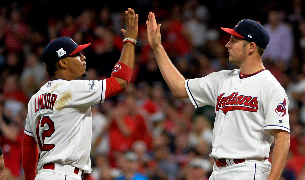 . Cleveland Indians\' Francisco Lindor, left, congratulates starting pitcher Trevor Bauer before Bauer left in the seventh inning of Game 1 of a baseball American League Division Series, against the New York Yankees on Thursday, Oct. 5, 2017, in Cleveland. Bauer pitched 6 2/3 innings and gave up two hits. (AP Photo/Phil Long)