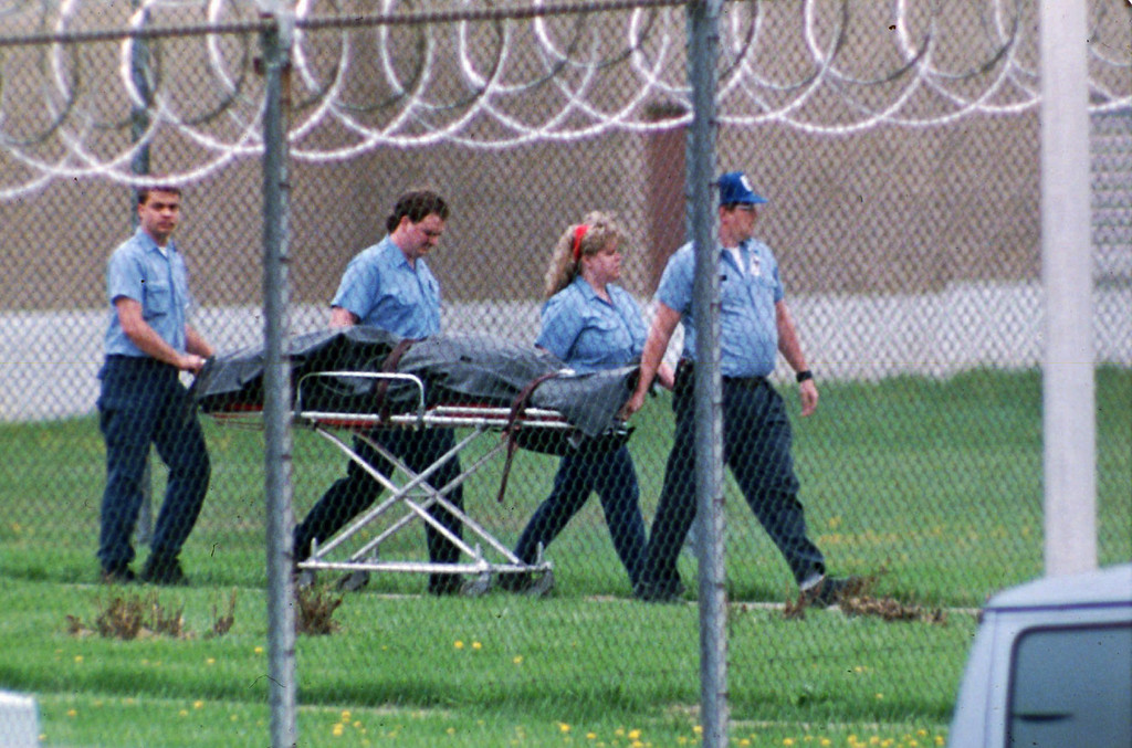 . FILE - This April 15, 1993 file photo shows the body of Southern Ohio Correctional Facility guard Robert Vallandingham carried from the prison in Lucasville, Ohio, after his body was found in the prison yard. In the 20 years since the nation\'s longest deadly prison riot broke out in Lucasville, no interviews have been granted with the five men sentenced to death in the killing of a guard. Yet time has brought new evidence and insights that will dominate events marking the 20th anniversary of the 11-day siege of April 1993. (AP Photo/Mark Duncan, File)
