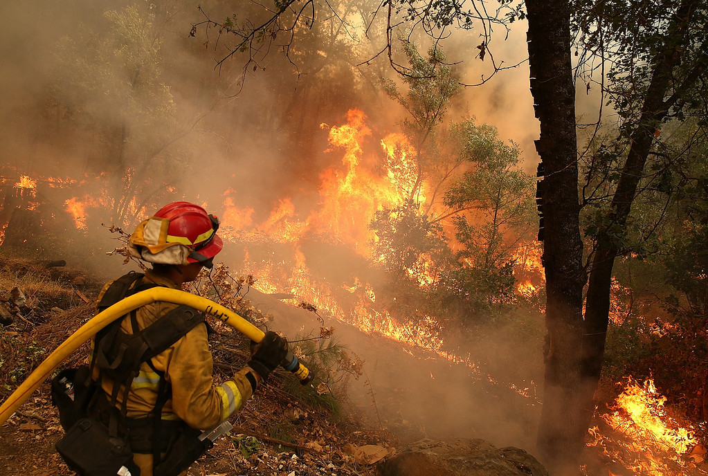 . GROVELAND, CA - AUGUST 21:  A firefighter from Ebbetts Pass Fire District monitors a back fire as he battles the Rim Fire on August 21, 2013 in Groveland, California. The Rim Fire continues to burn out of control and threatens 2,500 homes outside of Yosemite National Park. Over 400 firefighters are battling the blaze that is only 5 percent contained.  (Photo by Justin Sullivan/Getty Images)