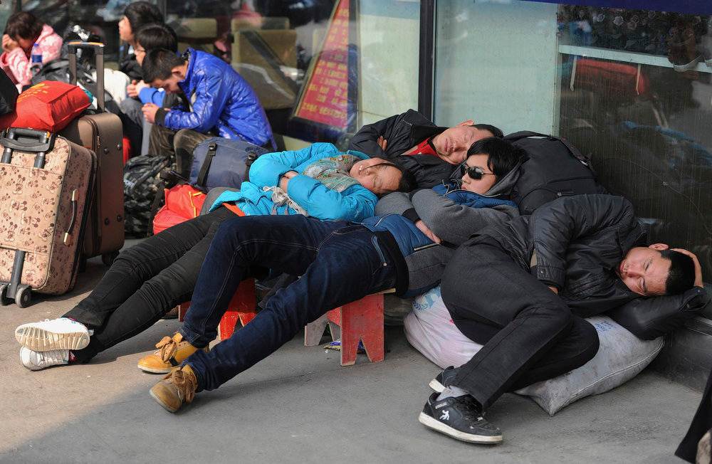 . Passengers sleep as they wait for their trains outside the train station in Hefei, Anhui province January 26, 2013. The 2013 Spring Festival travel peak began on Saturday and will last till March 6. According to the Ministry of Transport, over 3.1 billion people are expected to travel via road or water during this period, a year-on-year increase of 4 percent, local media reported. REUTERS/Stringer