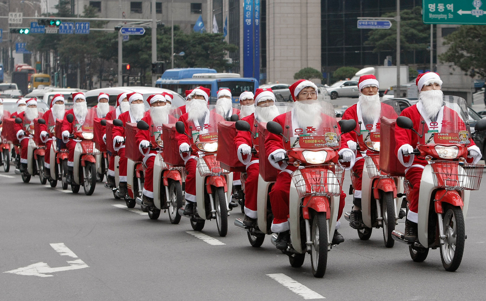 Description of . South Korean postmen dressed as Santa Claus on delivery bikes leave the post office headquarters to deliver Christmas gifts to poor people for their charity campaign in Seoul, South Korea, Monday, Dec. 13, 2010. The campaign that involved some 50 postmen will be expanded into nine cities until the end of this year. (AP Photo/Ahn Young-joon)