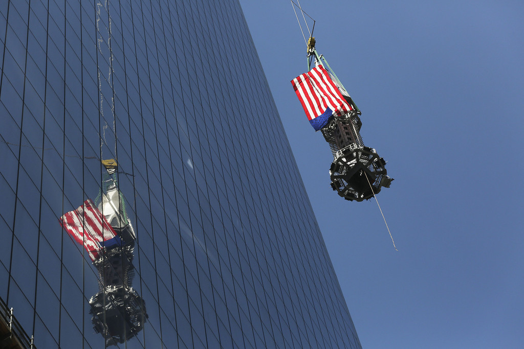 . The final piece of the spire is hoisted to the roof of One World Trade Center in New York, Thursday, May 2, 2013. The piece will be attached to the spire at a later date, capping off the tower at 1,776 feet. (AP Photo/Mark Lennihan)