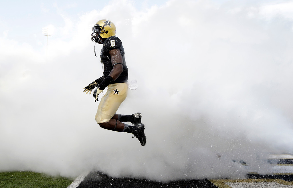 . Vanderbilt defensive back Darrius Sims jumps through smoke as the team is introduced before an NCAA college football game against Austin Peay on Saturday, Sept. 7, 2013, in Nashville, Tenn. (AP Photo/Mark Humphrey)