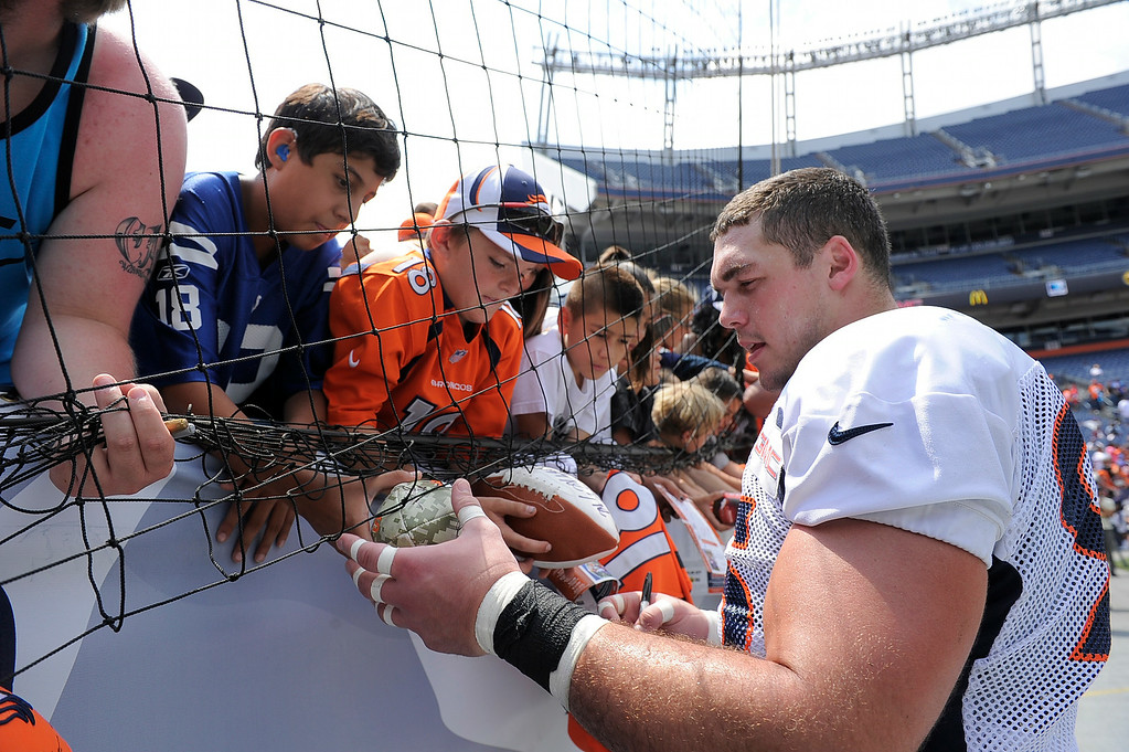 . Denver Broncos defensive end Derek Wolfe (95) signs autographs after practice on day four of the Denver Broncos 2014 training camp July 27, 2014 at Sports Authority Field at Mile High. (Photo by John Leyba/The Denver Post)