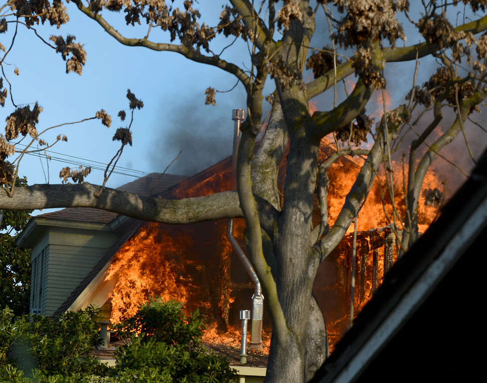 . Flames shoot from the back of a two-story home on fire in the 400 block of H Street  in Antioch, Calif., on Wednesday, March 13, 2013.  No one was home at the time of the blaze and no one was injured, according to firefighters on the scene. (Susan Tripp Pollard/Staff)
