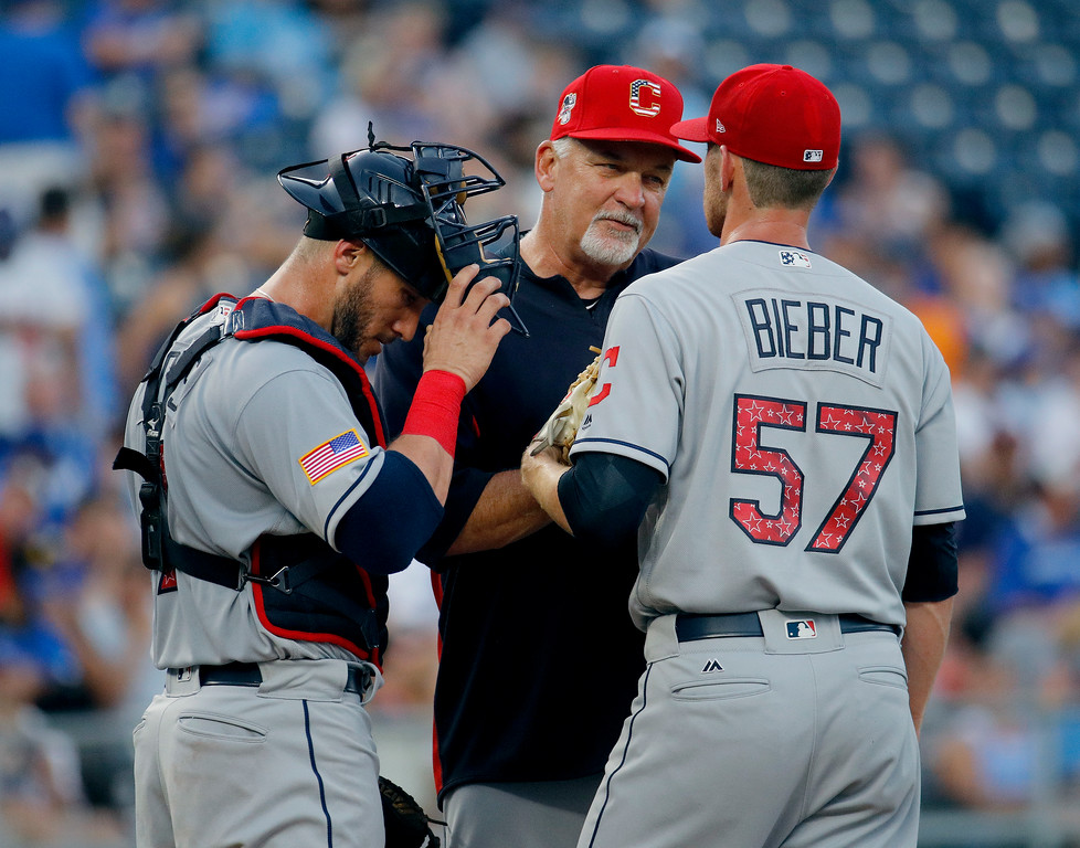. Cleveland Indians pitching coach Carl Willis talks to catcher Yan Gomes and starting pitcher Shane Bieber (57) during the second inning of the team\'s baseball game against the Kansas City Royals on Tuesday, July 3, 2018, in Kansas City, Mo. (AP Photo/Charlie Riedel)
