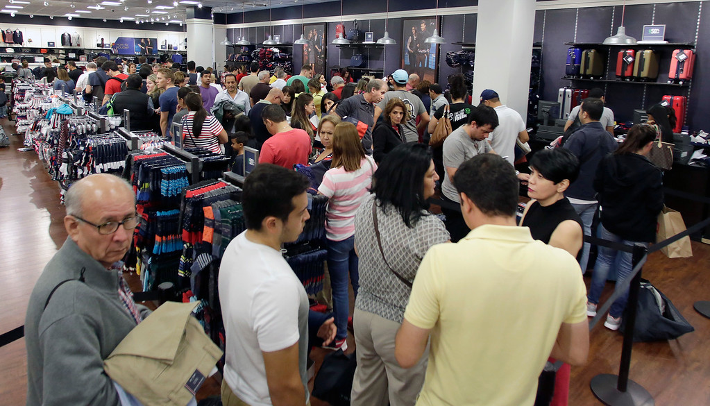 . Shoppers stand in line to pay for their purchased merchandise at a Tommy Hilfiger store on Black Friday, Nov. 25, 2016, in Miami. Stores opened their doors Friday for what is still one of the busiest days of the year, even as the start of the holiday season edges ever earlier. (AP Photo/Alan Diaz)