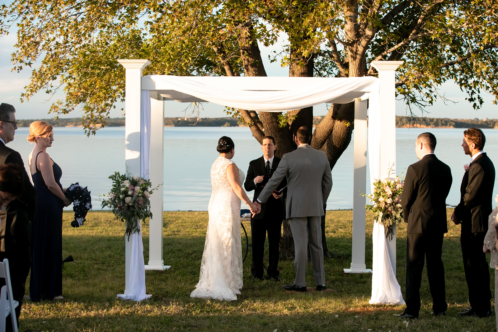 bride and groom standing under a white wedding arch shrouded in white fabric next to a lake for their wedding ceremony