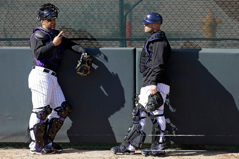 . Colorado Rockies\' Gustavo Molina talks Ramon Hernandez, right, during a break in a spring training baseball workout Tuesday, Feb. 12, 2013, in Scottsdale, Ariz. (AP Photo/Darron Cummings)